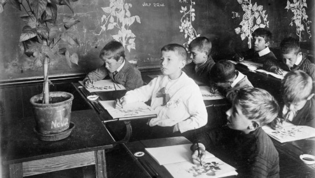 Boys engaged in a drawing class at an English school during the First World War. Their subject is a potted plant.