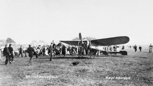 Bleriot monoplane on the ground with a large crowd of people looking at the aircraft.